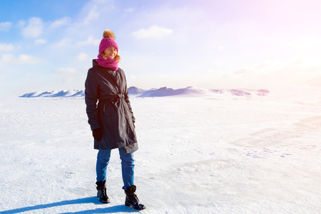 A young woman  in warm coat and  hat enjoys  winter nature, walking and chat on  snow in  frozen sunny day in the background of a snow mountains, blue sky and sunny Stock Photo