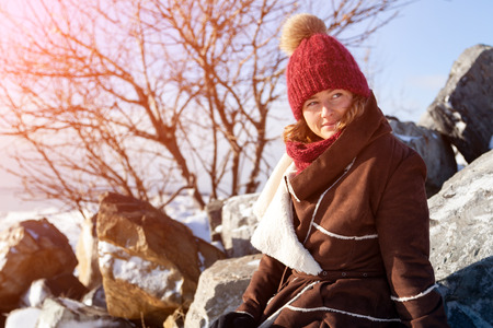 Outdoor close up portrait of young beautiful woman with long hair wearing hat,  coat posing om winter stone. Christmas, winter walking concept.