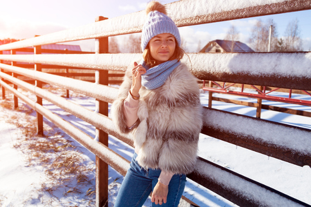 Winter young woman portrait. Beauty Joyful Model woman in hat and furcoat posing and laughing, having fun in winter park. Beautiful young woman laughing outdoors. Enjoying nature, wintertime Stock Photo