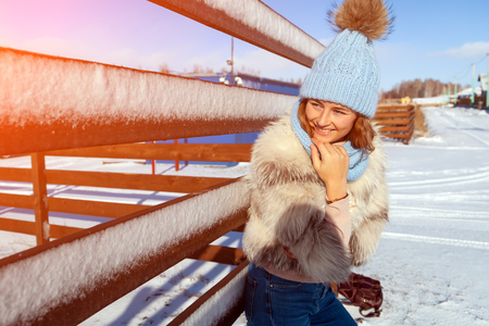 The concept of livestyle  outdoor in winter. A young woman student in a blue knitting hat and  furcoat  smiles, heats up and walks through the winter mountains Stock Photo