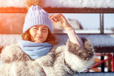 Emotive portrait of a fashionable model in white furcoat and knitting hat standing at the winter park Sunny weather. French style. Outdoor shot. Stock Photo