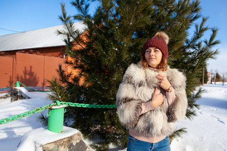Portrait beauty woman model on winter background. Beautiful modern urban young woman wearing blue knitting hat and white furcoat  basks in cold weather background of a fluffy Christmas tree Stock Photo