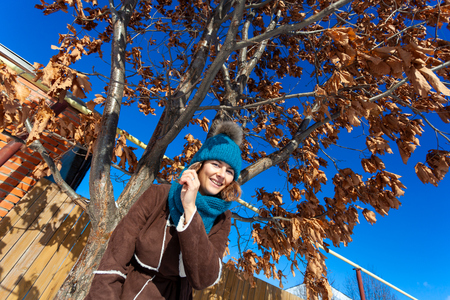 Emotive portrait of a fashionable model in  brown coat and knitting hat standing at the yellowed tree.  Sunny weather. French style. Outdoor shot.
