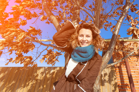 A young woman  in warm brown coat and  scarf enjoys  autumn nature, smiling and posing on  snow in  autumn sunny day in the background of a at the yellowed tree, blue sky and sunny Stock Photo