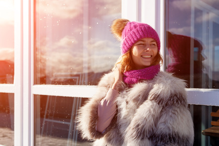 Fashion lifestyle portrait of young trendy woman dressed in warm stylish furcoat and knitting hat  laughing and smiling in the  winter street.  portrait of joyful woman Stock Photo