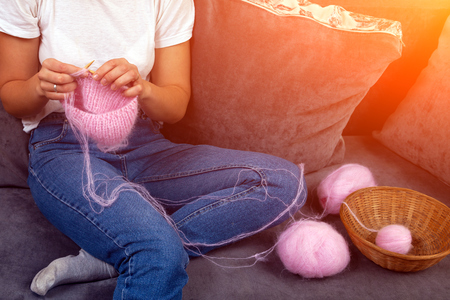 Close-up of woman hands knitting colorful  pink wool yarn. Close-up knitting photo. Freelance creative working and living concept Stock Photo