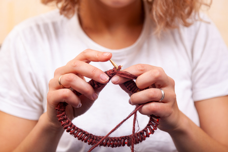 Close-up of a dark-haired beautiful woman smiling and knitting with knitting crochet from a natural woolen thread a  brown hat , a woman shows how to knit correctly