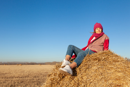 Autumn young woman portrait. Beauty Joyful Model woman in hat and pink coat posing, laughing, having fun and sitting on hay stick in  field.
