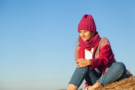 Fashion lifestyle portrait of young trendy woman dressed in warm stylish coat, knitting hat and jeans  posing and smiling on yellow a stack of hay.  portrait of joyful woman