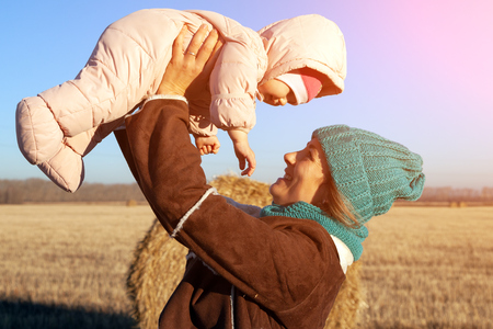 Autumn young mom portrait. Beauty Joyful Model woman in hat and  coat playing with her daughter in  field. Beautiful young woman laughing outdoors. Enjoying nature, autumn time