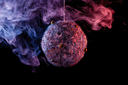 Close up  of a  silver shiny decoration Christmas balls in colored purple-blue smoke, on an isolated black background. Concept of a modern Christmas card. Happy new year disco-ball in colored smoke Stock Photo