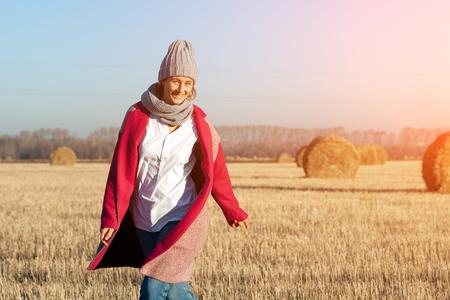 Outdoor close up portrait of young beautiful woman with long hair wearing gray hat,  pink coat posing on field in autumn park.  Autumn walking concept. Stock Photo