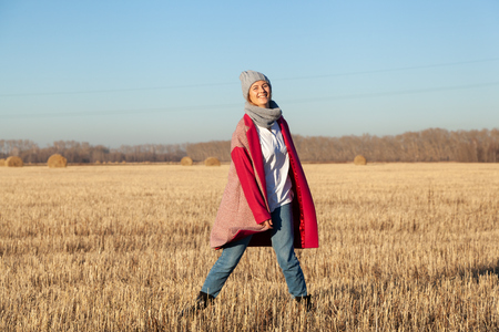Autumn young woman portrait. Beauty Joyful Model woman in hat and pink coat posing and laughing, having fun in  field. Beautiful young woman laughing outdoors. Enjoying nature, autumn time