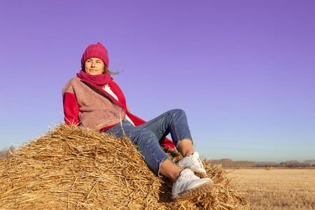 Autumn young woman portrait. Beauty Joyful Model woman in hat and pink coat posing, laughing, having fun and sitting on hay stick in  field. Beautiful young woman laughing outdoors. Enjoying nature, autumn time Stock Photo