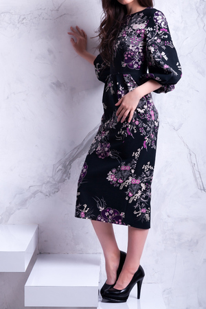 Sensual beautiful brunnete woman posing in black floral dress. Girl with long curly hair.Happy woman celebrate holiday