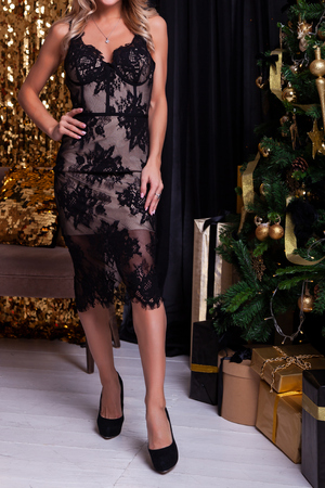 Young beautiful blond woman in a short black lingerie dress posing next to a Christmas tree with gifts, shiny decorations in the background. Ideas of a New Years dress for girls, New Years fashion trends