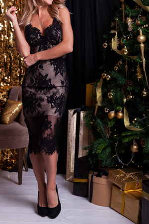 Young beautiful blond woman in a short black lingerie dress posing next to a Christmas tree with gifts, shiny decorations in the background. Ideas of a New Year's dress for girls, New Year's fashion trends