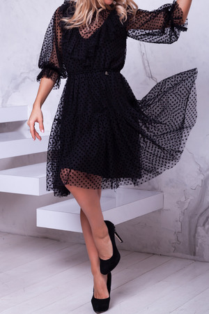 Ellegant girl with long beautiful hair in a black short dress with high heels  showing off her dress on studio background. Ideas of a New Years dress for girls, New Years fashion trends