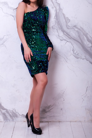 Portrait of attractive smiling girl showing  her shiny green dress .  New years feeling. Merry christmas. Happy woman celebrate holiday