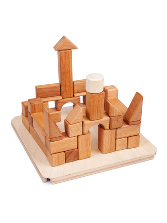 Photo wooden constructor of small cubes, triangles, balls and other forms of beech on a white isolated background. Wooden designer, built in the shape of the castle