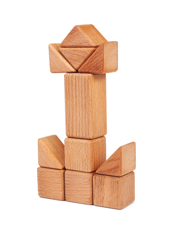 Photo wooden constructor of small cubes, triangles, balls and other forms of beech on a white isolated background. Wooden constructor, folded in the form of a tower