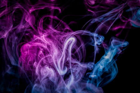 Cloud of pink and blue smoke on a black isolated background. Background from the smoke of vape 免版税图像