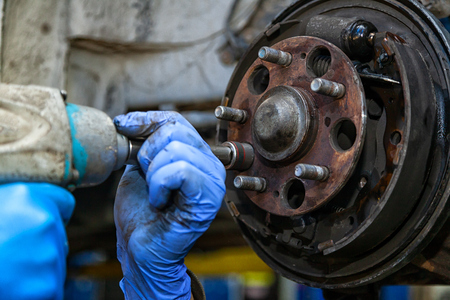 Close-up replacement of the old front brake disc, brake caliper and hub nut on a car raised on a lift with a pneumatic wrench in a car repair shop. Auto mechanic repair.