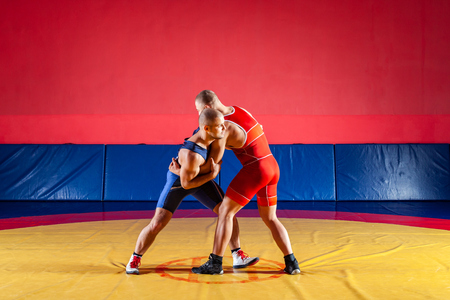 The concept of fair wrestling. Two greco-roman  wrestlers in red and blue uniform wrestling  on a yellow wrestling carpet in the gym Stock Photo