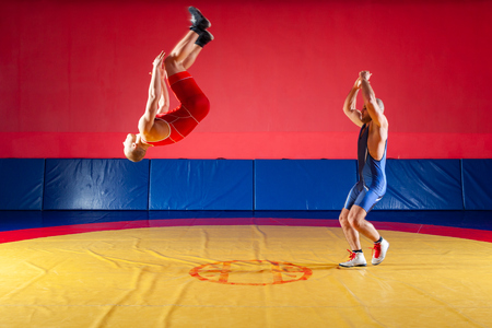Two strong wrestlers in blue and red tights make flips and jumps on the yellow wrestling track in the gym. A young man makes a grab.