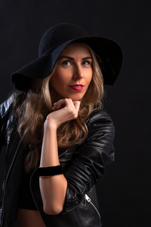 Smiling beautiful young woman in in trendy black T-shirt, orange skirt, leather jacket and black hat  posing with hands on chin. Three quarter length studio shot on  black background
