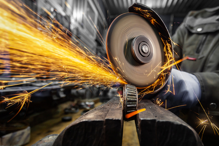 A close-up of a car mechanic using a metal grinder to cut   bearing in an auto repair shop, bright flashes flying in different directions. Work of auto mechanics.