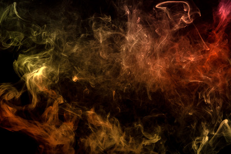 Cloud of red and orange smoke on a black isolated background. Background from the smoke of vape