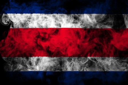 National flag of Costa  Rica from thick colored smoke on a black isolated background Imagens