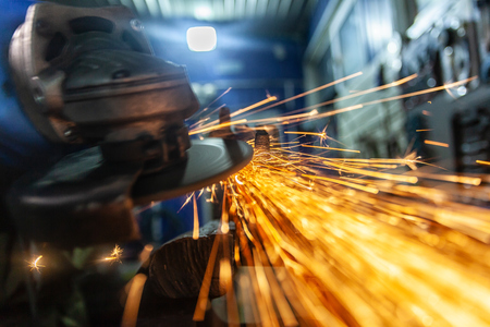 Un gros plan d'un mécanicien automobile utilisant une meuleuse en métal pour couper le roulement dans un atelier de réparation automobile, des éclairs lumineux volant dans différentes directions. Travaux de mécanique automobile.