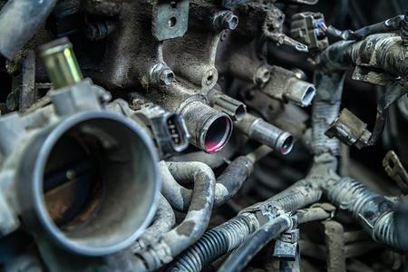 Primo piano del guasto del motore: antigelo rosa scorre dai tubi del motore di una vecchia auto Archivio Fotografico