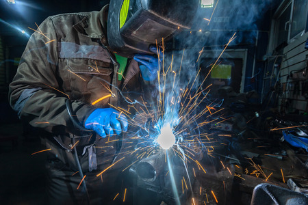 Man welder in welding mask, building uniform and blue protective gloves welds metal car muffler with welding machine in auto repair shop, in the background construction site