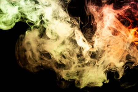 Colorful yellow and orange smoke  on a black isolated background. Background from the smoke of vape 免版税图像