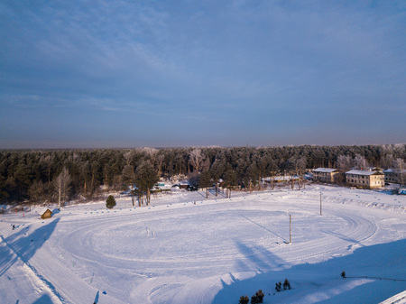 Helicopter drone shot. Aerial photography of green forest  and stadium with road, house in cold winter day.