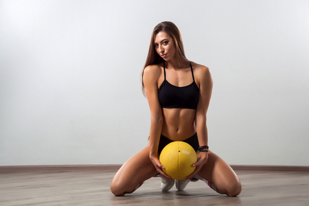 Dark-haired young woman fitness model in black sports top and  shorts demonstrates her  figure  and seductively posing with ball on white isolated background Stock Photo