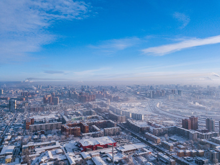 Aerial photography of a modern city: high-rise buildings, a big road, shops and parks on a cold  winter day with a blue sky.Helicopter drone shot Stock Photo