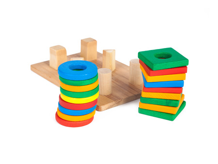Photo of a wooden toy  children's sorter with small wooden details in the form of geometric shapes (rectangle, square, circle, triangle), in different colors  on a white isolated background