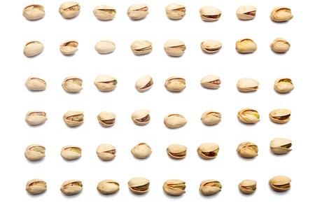 A collection of pistachio nuts lie in horizontal rows on an isolated white background. with clipping path. Pistachio pattern Imagens