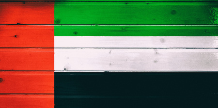 National flag of United Arab Emirates  on a dull wooden background