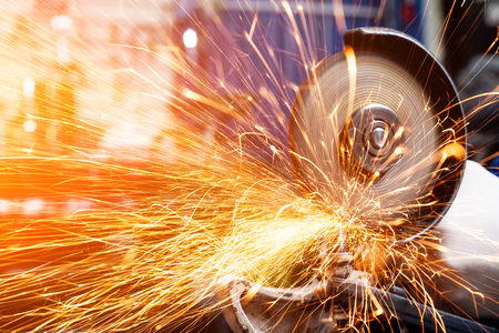Close-up on the sides fly bright sparks from the angle grinder machine. A young male welder in a white working gloves grinds a metal product with angle grinder in the garage Stockfoto
