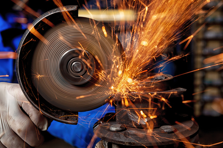 Close-up of a man sawing metal with a hand circular saw,  bright flashes flying in different directions, in the background tools for an auto repair shop. Work of auto mechanics. Фото со стока