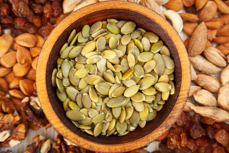 Peeled pumpkin seeds in a wooden cedar plate on the background a scattering of various nuts. Peeled pumpkin seeds pattern Zdjęcie Seryjne