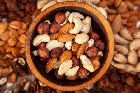 Peeled  hazelnut, cashew, almond  in a wooden cedar plate on the background a scattering of various nuts. Peeled hazelnut, cashew, almond pattern