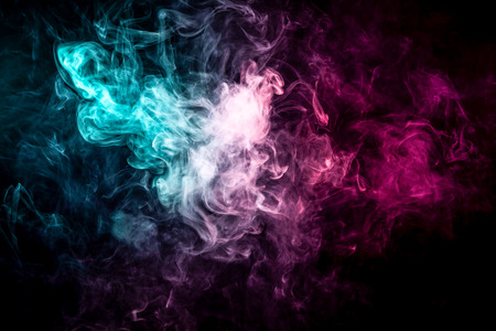 Close up swirling pink and blue smoke on black isolated background