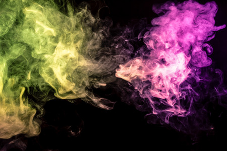 Abstract art colored  yellow and pink smoke on black isolated background. Stop the movement of multicolored smoke on dark background Stock Photo