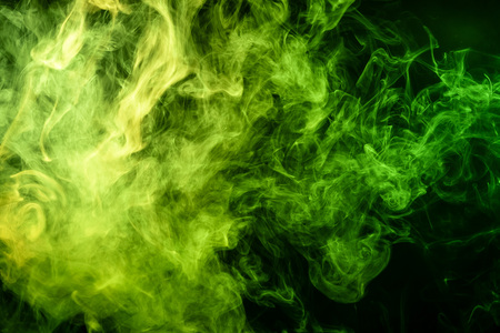 Abstract art colored  green smoke on black isolated background. Stop the movement of multicolored smoke on dark background Stock Photo